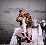 Joe Reynolds and a nice fly-caught striped bass near the Route 50 Bridge in Ocean City, Maryland. 2005.